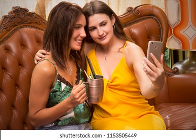 Young women couple friends taking selfie and sharing with cocktail drinksat pub bar restaurant.