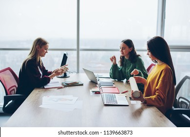 Young women crew of designer having informal meeting for discussing startup ideas together, smart female colleagues communicating at desktop using modern technology and wireless connection in office