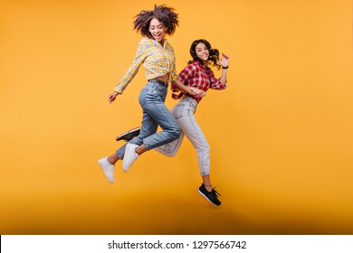 Young women with curly hair run on orange background. Models in streetwear posing in jump