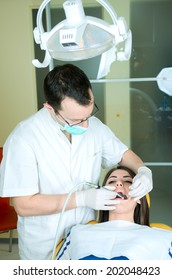 young women to the dentist in the dental chair sits next to a doctor to do the dentist to see if his teeth were okay/young women to the dentist