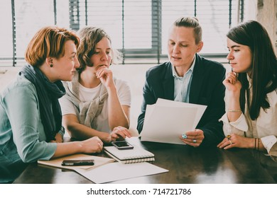 Young women discussing documents in creative office. Successful feminine teamwork and business brainstorming concept. Toned image