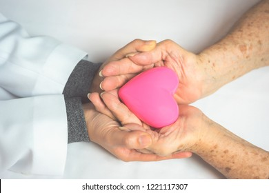 Young women doctor and eldely hands holding pink heart. Medical and healthcare concept
