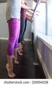 Young women doing barre exercises