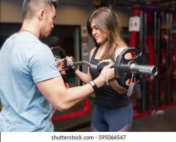Young women doing biceps weight training with coach