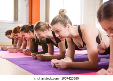 Young women doing exercise for abdominal. Athletic class doing abs in a row.