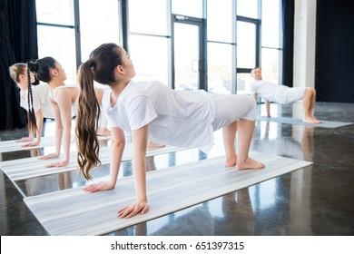 young women doing Half-wheel pose (Ardha Chakrasana) with instructor indoors