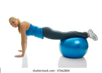 Young women doing pushups on fitness ball. Isolated on white
