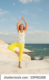 Young women doing yoga by the sea - Tree pose (Vrikshasana)