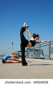 young women doing yoga on a pier