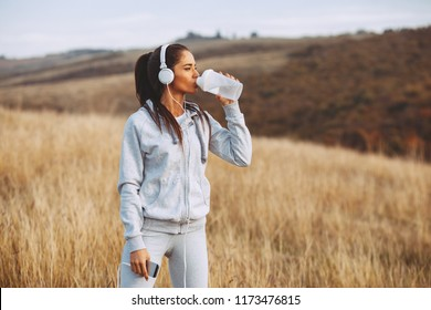 Young women drink water after jogging in nature