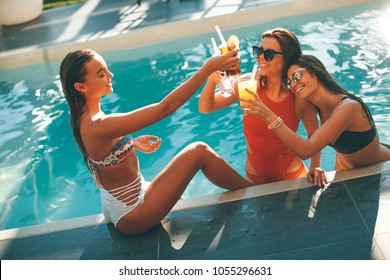Young women drinking coctail and having fun by swimming pool at hot summer day