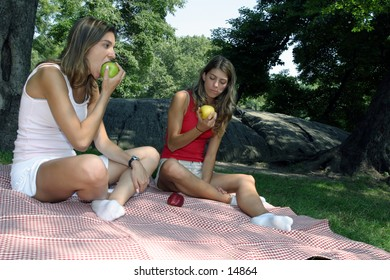 young women eating a green apples