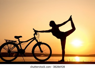 Young women is engaged in yoga on seacoast on a sunset