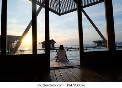 Young women enjoy the sunset on the edge of the cottages at Pulo love Gorontalo Indonesia resorts