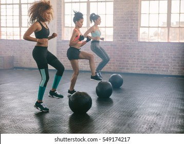 Young women exercising in aerobics class with medicine balls on floor. Three females doing workout together in gym.