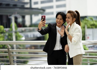 Young women face time or video call with friend outdoor. The working lady call to parent with cell phone.