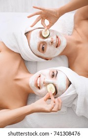 Young women with facial masks and cucumber slices in spa salon
