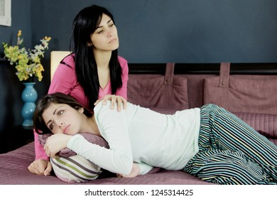 Young women feeling sad holding each other
