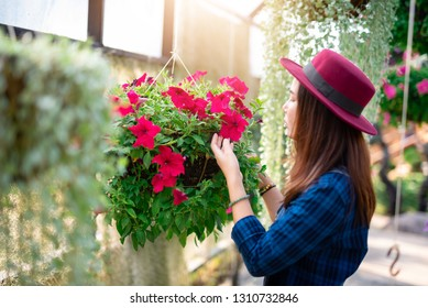 Young women and flower care in the garden that are blooming in the morning