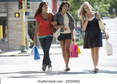 Young women friends shopping and texting on a cell phone