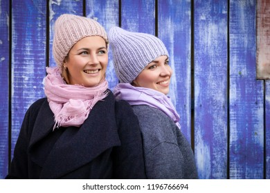 A young women friends in a stylish clothes   pose, smile  and  look at the camera  around blue wall. The concept of livestyle and outdoor recreation in autumn