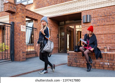 A young women friends in a stylish clothes   walking, chat  and drink coffee to go om old brick city. The concept of livestyle and outdoor recreation in autumn