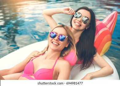 Young women friends in the swimming pool fun