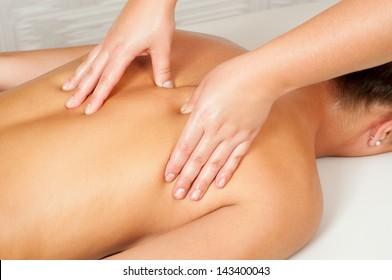 Young women getting back massage in massage salon.