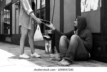 A young women give food for homeless man,Homeless man happy with food from humanitarian woman