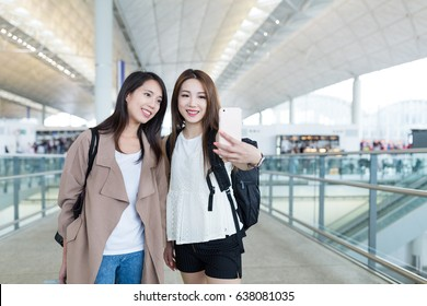 Young women go travel together and taking selfie in Hong Kong airport