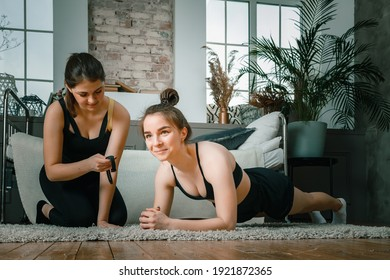 Young women goes in for sports at home, training online. Home workout with a friend, the trainer monitors the plank time on the stopwatch