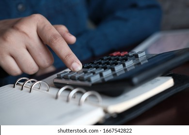 young women hand use calculator and notepad on desk