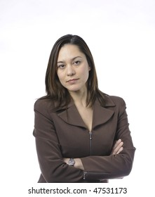 Young women has her arms crossed.She is of mixed race.Wearing a brown suit and has long brown hair.