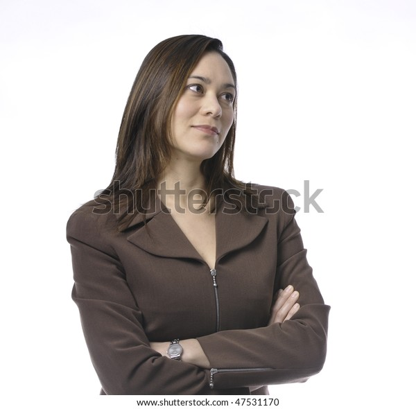 Young women has her arms crossed.She is of mixed race.Wearing a brown suit and has long brown hair.Her head is turn sideways.It is on a white background.She has a small smile.