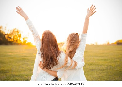 Young women are having fun on the green field in the evening.
