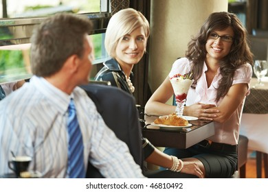 Young women having sweets in cafe, talking with businessman sitting at next table, smiling. Selective focus on women.