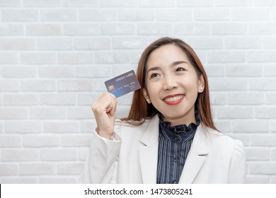 Young women holding credit card and thinking about online shopping via creditcard, Online shopping and marketing concept