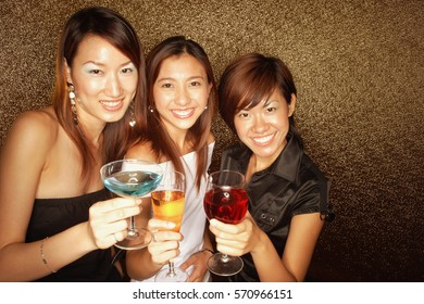 Young women holding drinks, smiling and looking at camera