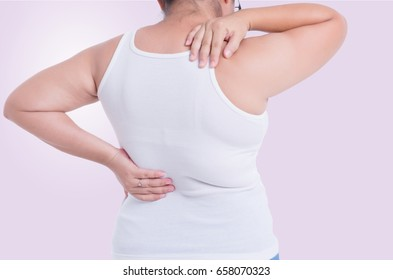 young women holding her back in pain. isolated on violet background.