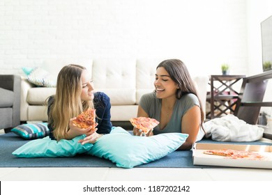 Young women holding pizza slices while lying on floor during party at home