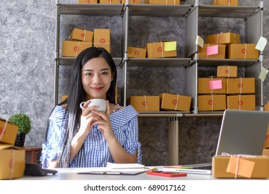 Young Women holding a white coffee mug small business owner working at home office packaging on background. online shopping SME entrepreneur or freelance working concept.
