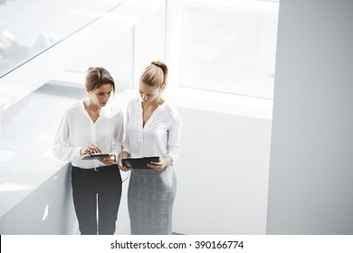 Young women leaders are checking financial statements from paper documents and portable touch pad. Two female confident business worker are using digital tablet for preparing to conference with staff