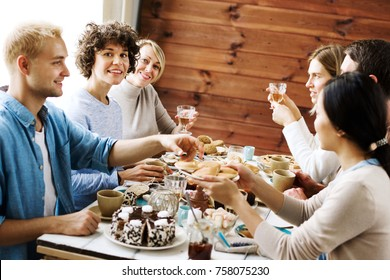 Young women looking at camera while sitting by xmas dinner table among their friends