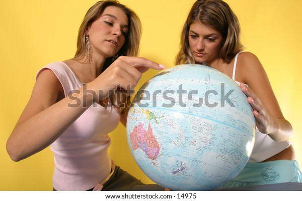 young women looking at globe