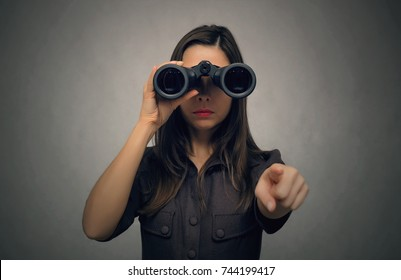 Young women looking through binoculars and showing ahead by her index finger. Find and search. Find something interesting.