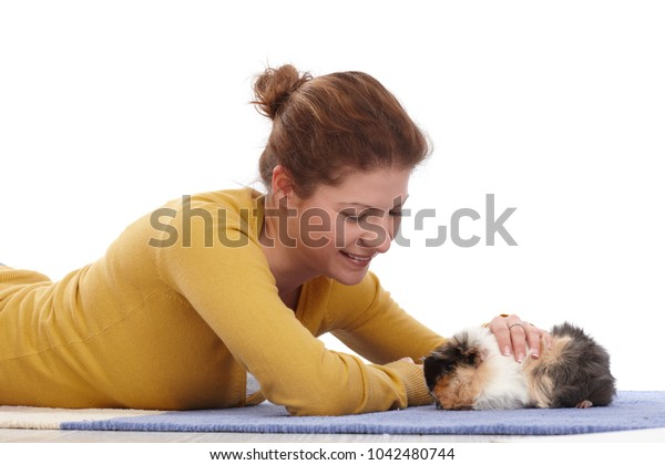 Young women lying on floor with guinea pig.