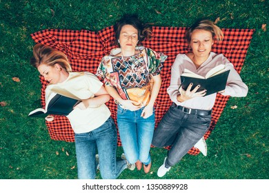 young women lying on the grass enjoying freedom and togetherness reading books and listening to music - real people life