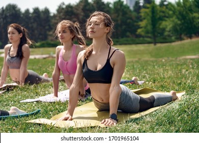 Young women maintaining healthy lifestyle practice yoga outdoors lying on mat making cobra pose stretching belly concentrated