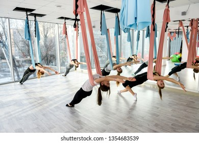 Young women making antigravity yoga exercises in group