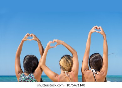 Young women making heart symbol with the hands at the beach